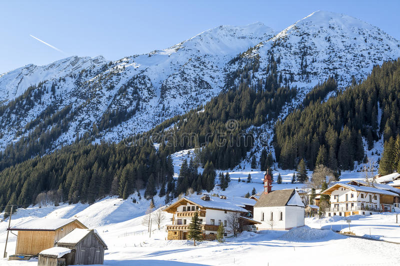 Alps, mountain range covered in the snow, alpine villag. Austrian Alps, mountain range covered in the snow, alpine village royalty free stock image