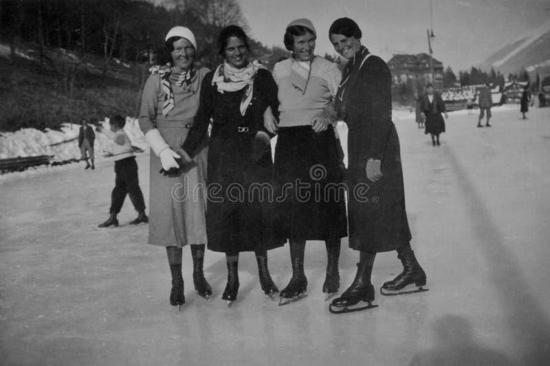 ALPS, SZWAJCARIA, 1932 - Cztery uśmiechniętej dziewczyny jeździć na łyżwach na wakacje w Szwajcarskich Alps obrazy stock