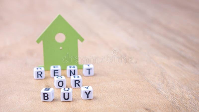 ALQUILE O COMPRE la palabra de las letras del cubo delante de símbolos de la casa verde en superficie de madera Concepto imagen de archivo libre de regalías