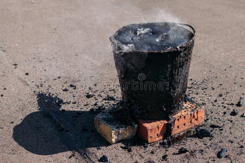 Alquitrán caliente fundido en un cubo en los ladrillos Reparación del tejado fotografía de archivo