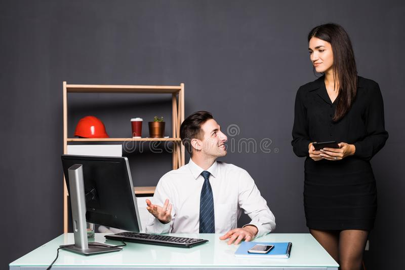 We already have great results. Young beautiful woman pointing at laptop with smile and discussing something with her coworker whil stock photography