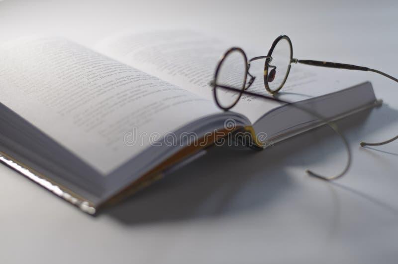 Alrededor de los vidrios viejos ponga en un libro blanco abierto, que miente en un fondo blanco fotografía de archivo libre de regalías