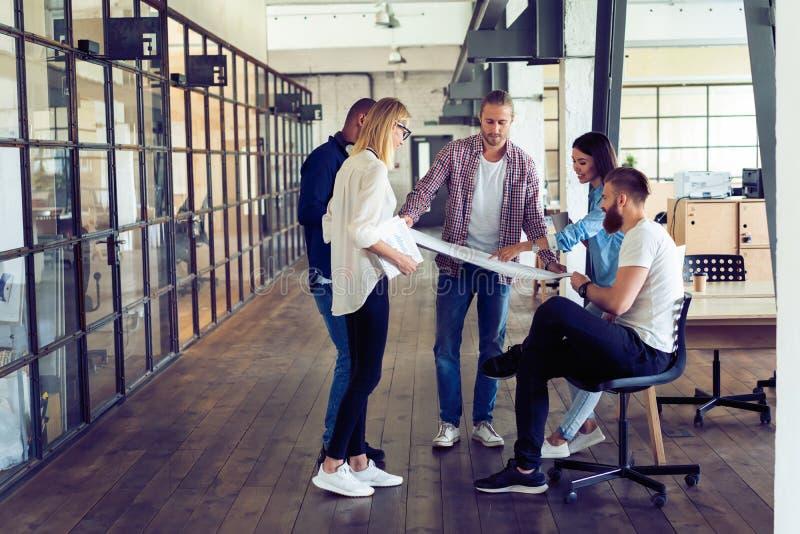 Als groep het werken Volledige lengte van jonge moderne mensen in slimme vrijetijdskleding plannings bedrijfsstrategie terwijl jo royalty-vrije stock foto's