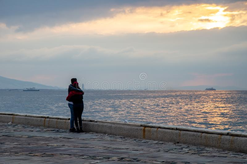 A young couple hugging each other is watching the sea and the city. royalty free stock photography