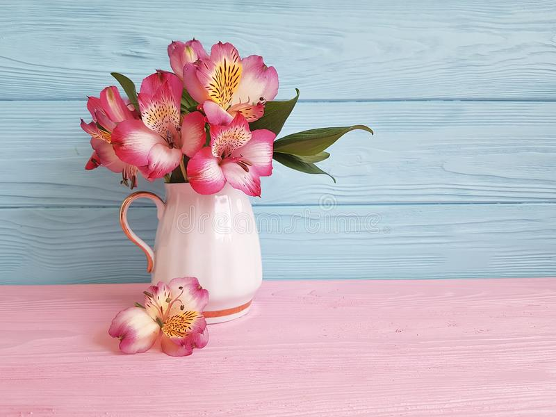 Alstroemeria de feuille de ressort de fleur de vase saisonnier sur une disposition en bois photo libre de droits