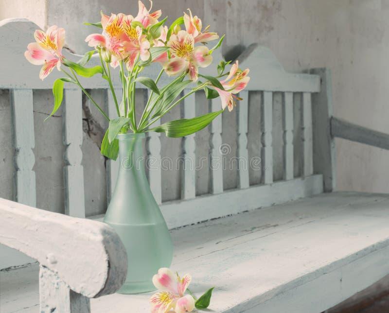 Alstroemeria en florero en banco de madera viejo imagen de archivo