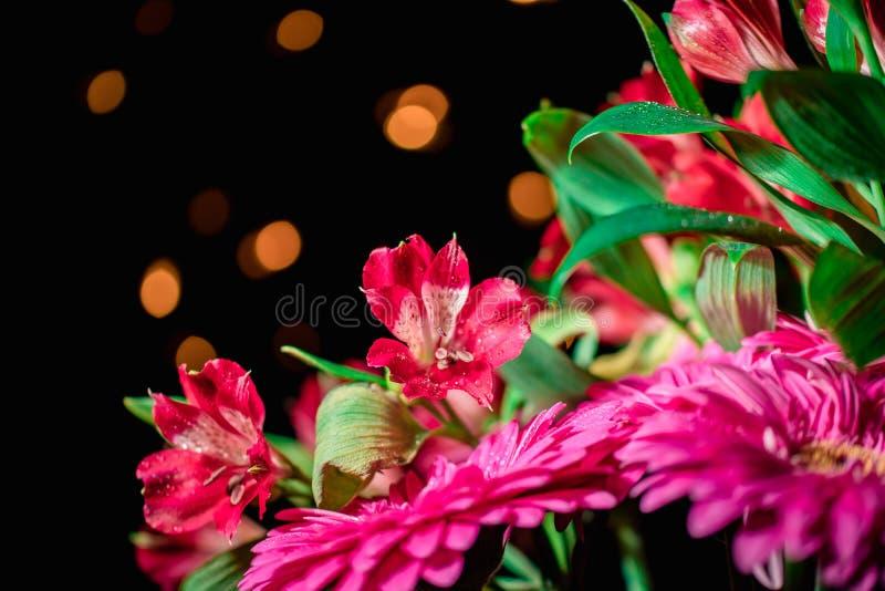 Alstroemeria- und Gerbera-Blumen mit Wassertropfen auf schwarzem Grund lizenzfreies stockfoto