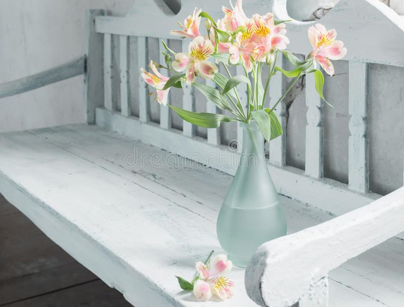 Alstroemeria in vase on wooden bench royalty free stock photography