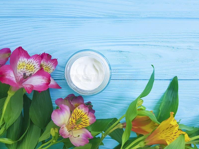 Alstroemeriablomma, kosmetisk kräm för skydd på en träbakgrund royaltyfri fotografi