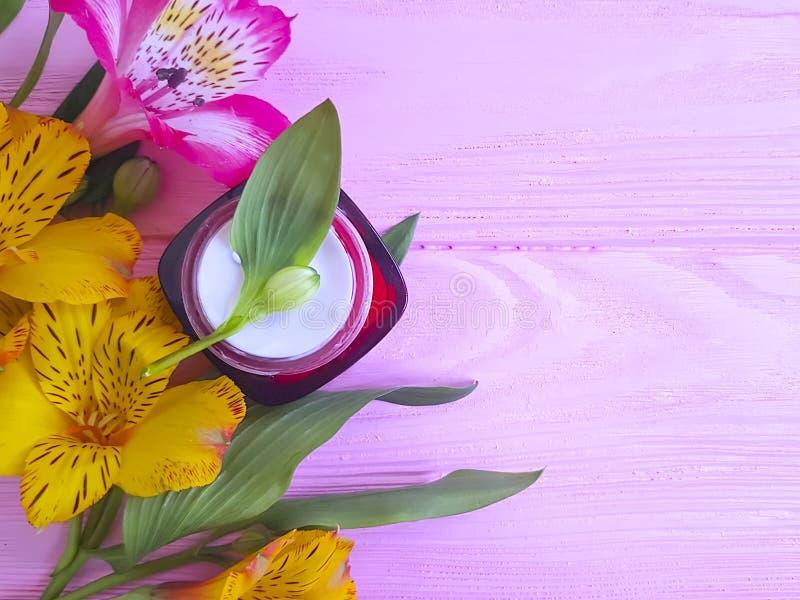 Alstroemeriablommablad, organisk skyddskräm för fuktighetsbevarande hudkräm på en ny träbakgrund fotografering för bildbyråer
