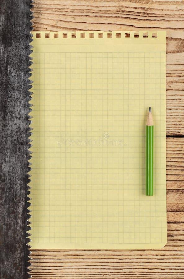 Alt sah und ein St?ck des Notizbuches lizenzfreie stockfotografie