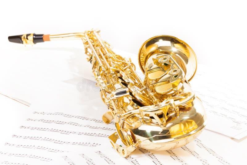 Alt- saxofon som lägger på de musikaliska anmärkningarna arkivfoto