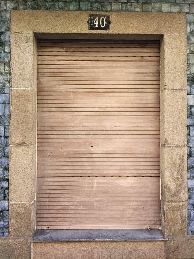 Alt und Weinlese schloss Fenster mit hölzernem Fensterladen in einer Granitsteinwand und in blauen Fliesen, mit Nr. 40 auf die Ob lizenzfreies stockbild