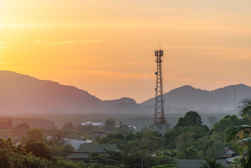 Alta antena de la torre de la célula de la telecomunicación en naturaleza asiática del campo en el fondo de las siluetas de las m foto de archivo libre de regalías