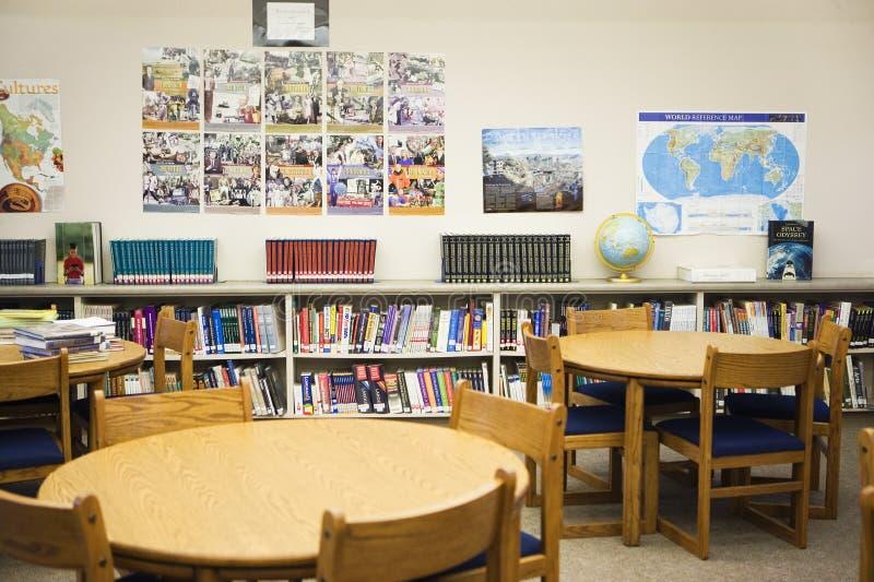 Alta biblioteca escolar con las tablas y las sillas dispuestas fotografía de archivo libre de regalías