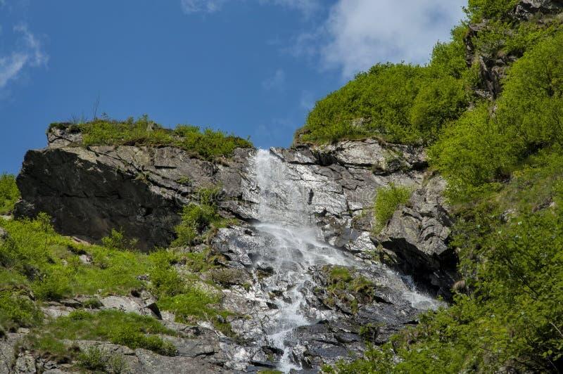 Alta cascata in montagne di Carpathians sotto cielo blu immagine stock libera da diritti