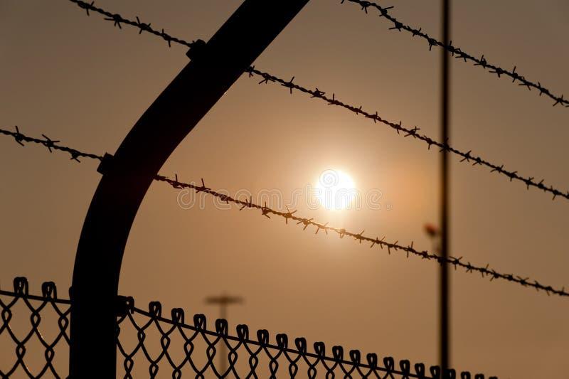 Alta cerca con alambre de púas en puesta del sol fotografía de archivo