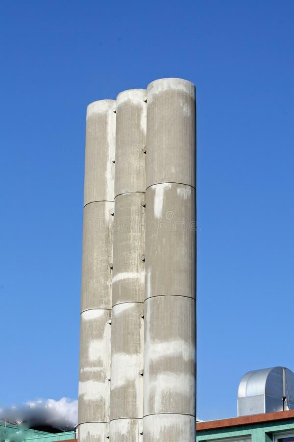 Alta chimenea concreta tres con un contexto del cielo imagen de archivo libre de regalías