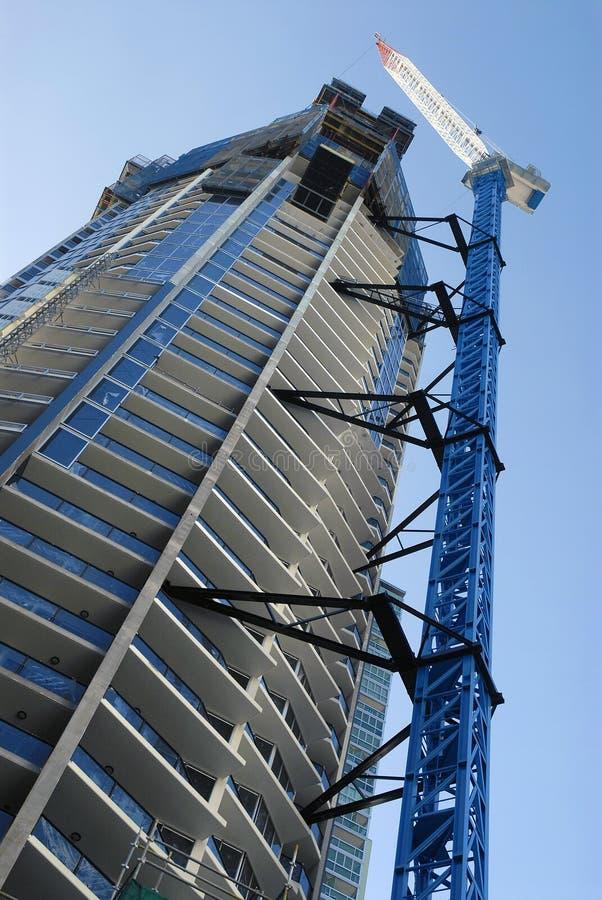 Alta construcción de edificios de la subida del rascacielos alto con la grúa, vertical imagen de archivo