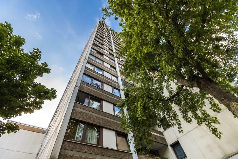 Alta construcción de viviendas de varios pisos con los árboles contra el cielo azul imágenes de archivo libres de regalías