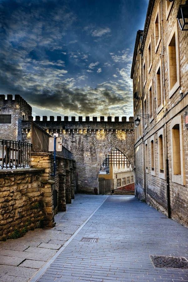 Alta fotografia della gamma dinamica di una via nella parte anziana di Vitoria, Spagna, con la parte di una parete merlata e suo immagine stock