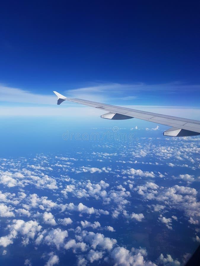 Alta manera que vuela sobre el cielo con las nubes hermosas imagenes de archivo