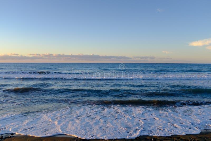 Alta marea durante una puesta del sol imagenes de archivo