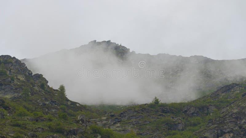 Alta montaña rodeada por el myst foto de archivo