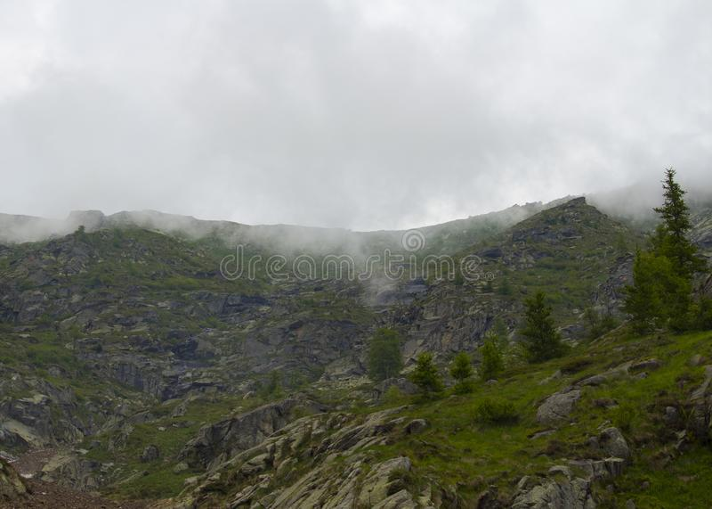 Alta montaña rodeada por el myst imagenes de archivo