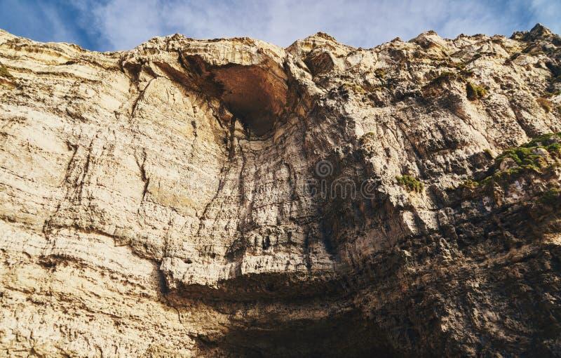 Alta pared de la roca con la cueva imágenes de archivo libres de regalías
