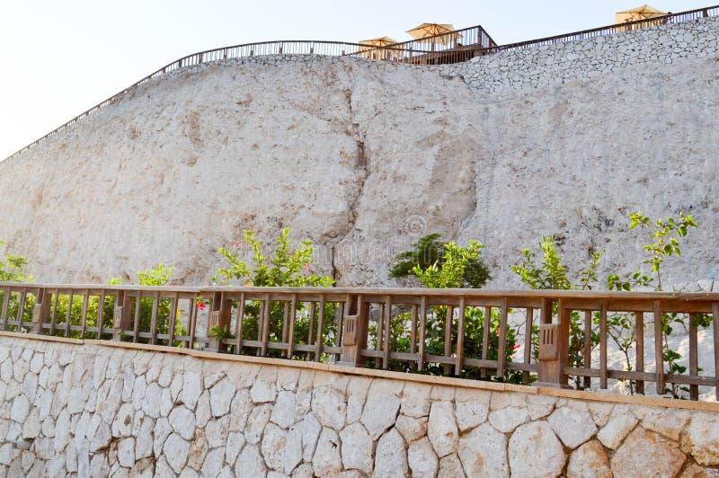 Alta pared de piedra ligera con los carriles de madera y una roca escarpada contra la perspectiva de los paraguas del sol y del c imagen de archivo