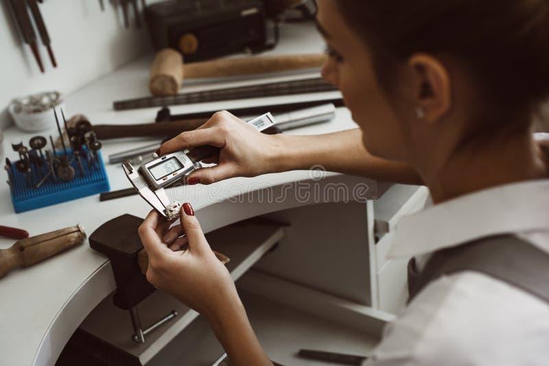 Alta precisión Foto ascendente cercana de un anillo de medición del joyero de sexo femenino joven con una herramienta en taller imagen de archivo