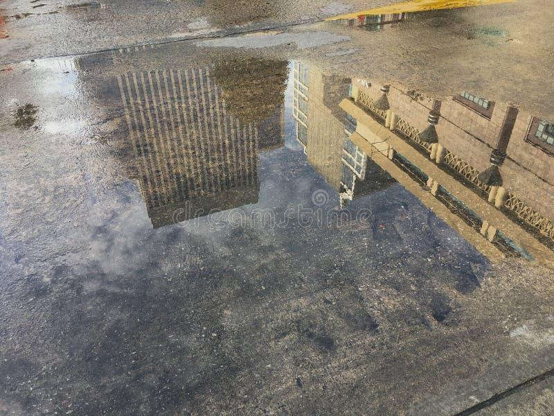 Alta reflexión del edificio en el piso mojado imagenes de archivo