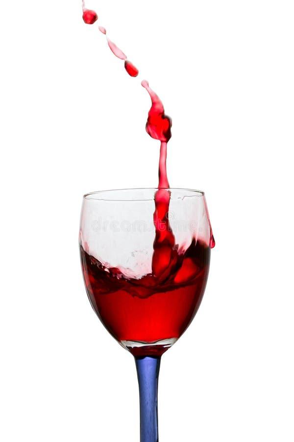 Alta spruzzata di vino rosso in un vetro con un gambo colorato su un fondo bianco fotografie stock libere da diritti