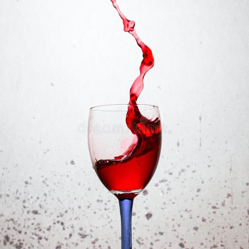 Alta spruzzata di vino rosso in un vetro con un gambo colorato su un fondo grigio fotografia stock
