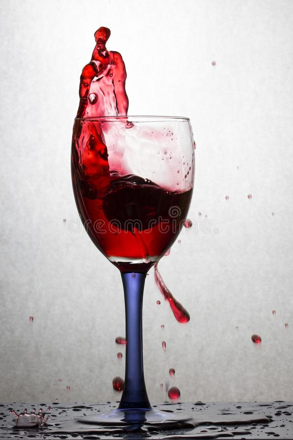 Alta spruzzata di vino rosso in un vetro su un fondo grigio fotografia stock