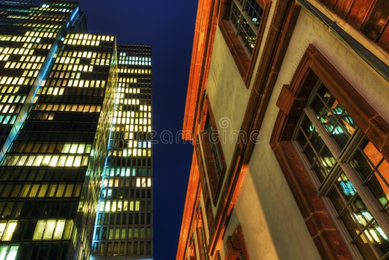 Alta subida moderna y edificio histórico en la noche fotos de archivo libres de regalías