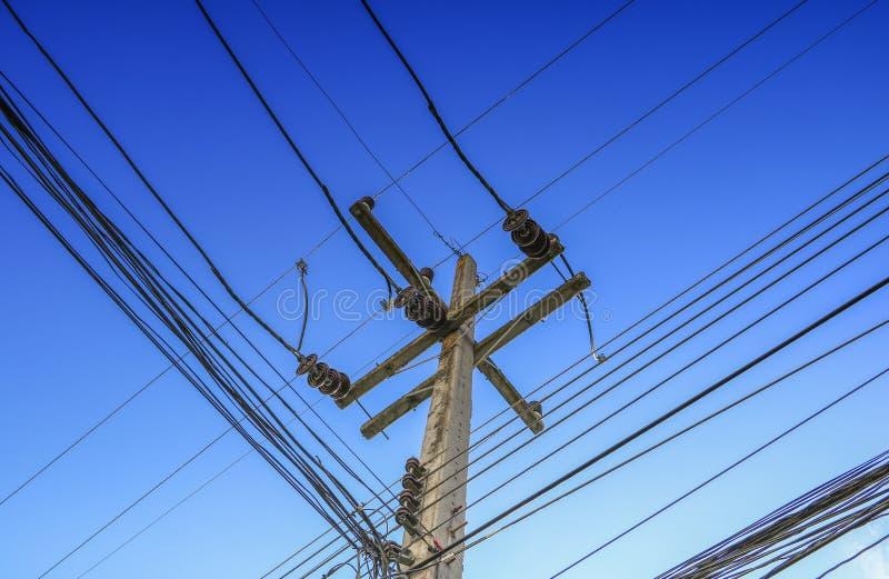 A alta tensão e o cabo do cargo da eletricidade alinham no céu azul fotos de stock royalty free