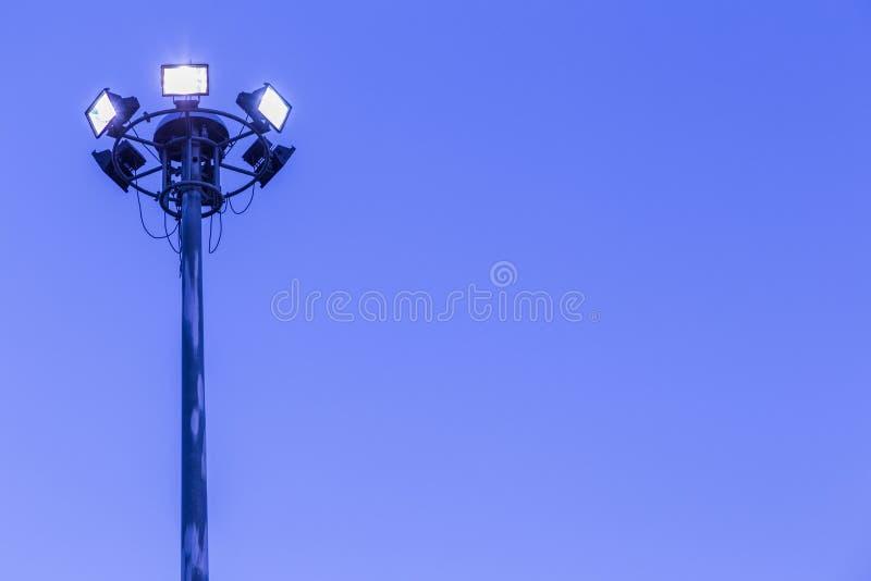Alta tensione della torre dei riflettori nello stadio di sport sul fondo del cielo blu fotografie stock libere da diritti