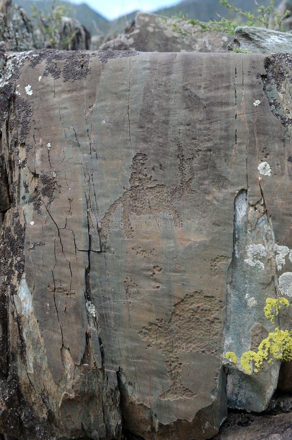Rock petroglyphs in the tract Kalbak-Tash. ALTAI REPUBLIC, RUSSIA - JUNE 8, 2018: Rock petroglyphs in the tract Kalbak-Tash. Petroglyphs of different historical stock photography