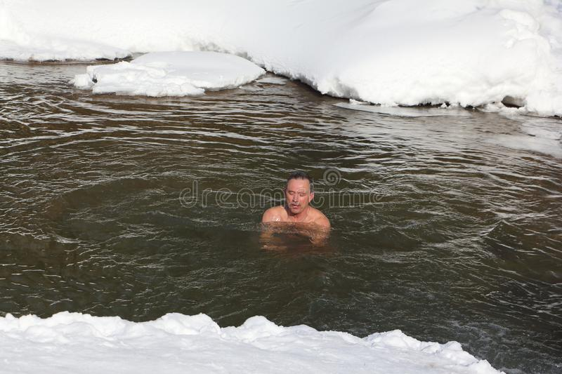 Cold trainings, man swimming in the Belokurikha River. Taken on - March, 11, 2017 in Altai Territory, Belkurikha city, Russia. Altai Territory, Belkurikha city stock images