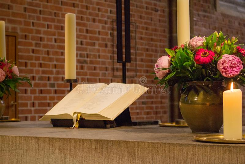 Altar bonito na catedral católica A Bíblia Sagrada aberta com flores, velas e cruz Decoração elegante da igreja fotografia de stock