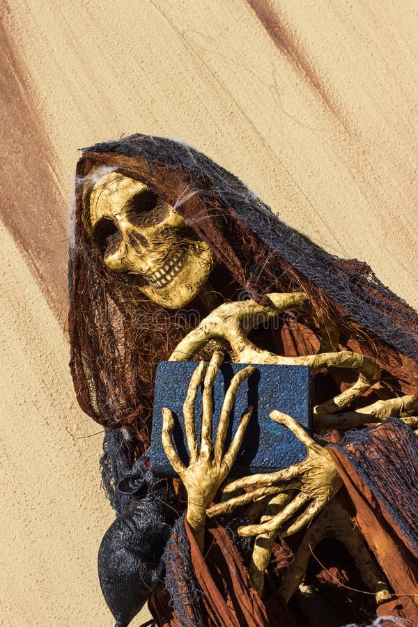 Altar con el cráneo hecho del libro y del rosario de la tenencia de papel imagen de archivo
