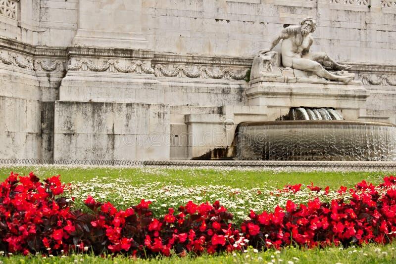 Altare della patria o del Vittoriano in piazza Venezia a Roma Dettaglio di una scultura e un prato con erba ed i fiori rossi immagini stock libere da diritti