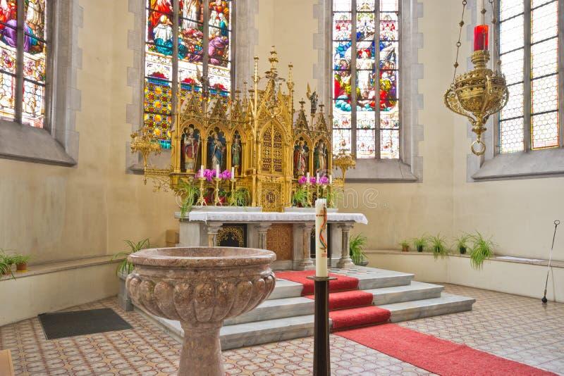 Altare och dopfunt i katolsk kyrka royaltyfri bild