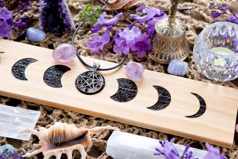 Altare pagano di fasi lunari della strega con il cristallo, i fiori ed il pentacolo fotografia stock libera da diritti