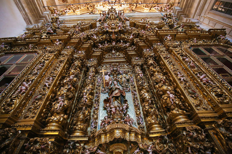 Altarpiece in the New Cathedral of Coimbra. Huge, magnificent gilt wood altarpiece in the national Portuguese artarpiece style, in the New Cathedral or Se Nova stock photo