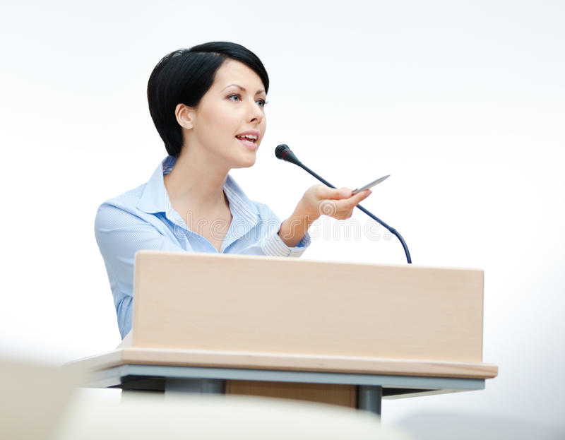 Altavoz bonito de la mujer en el podium imagenes de archivo