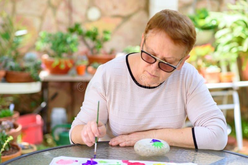 Alte ältere Frau, die den Spaß malend im Kunstunterricht im Freien hat stockfoto