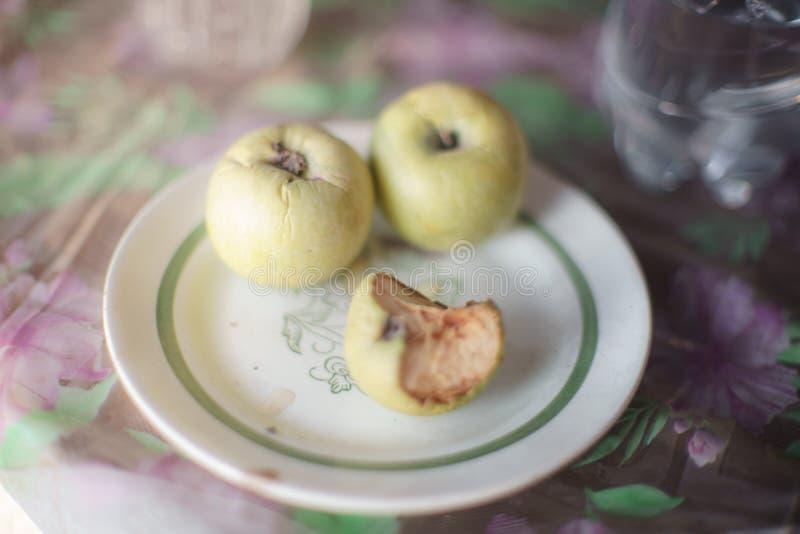 Alte Äpfel in einer Platte auf dem Tisch mit einer Tischdecke stockfotografie